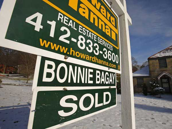 In this Thursday, Jan. 9. 2014, photo, a sold sale sign hangs in front of a house in Mount Lebanon, Pa. The Commerce Department releases new home sales for January on Wednesday, Feb. 26, 2014. (AP Photo/Gene J. Puskar)
