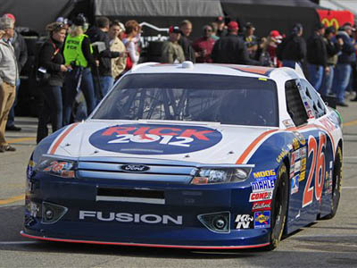 Driver Tony Raines drives his car, sponsored by Republican presidential candidate Rick Santorum, out to the track during practice for Sunday´s Daytona 500 auto race in Daytona Beach, Fla., Saturday, Feb. 25, 2012. (AP Photo/John Raoux)