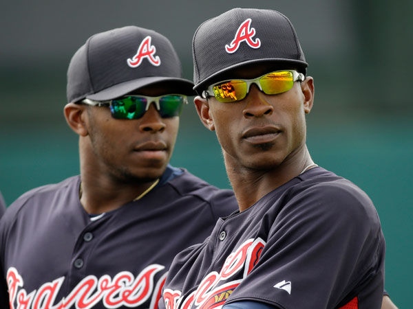 Atlanta Braves outfielders Justin Upton, left, and his brother B.J. Upton, right, listen to a coach during a spring training baseball workout Wednesday, Feb. 20, 2013, in Kissimmee, Fla. (David J. Phillip/AP)