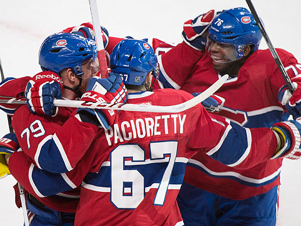 The Canadiens´ Max Pacioretty (67) celebrates with teammates Andrei Markov, left, and P.K Subban after scoring against the Toronto Maple Leafs during overtime of an NHL hockey game in Montreal, Saturday, March 1, 2014. (AP Photo/The Canadian Press, Graham Hughes)