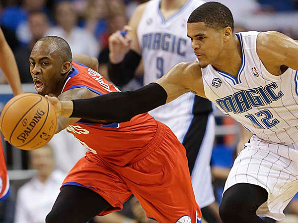 The 76ers´ James Anderson, left, and Orlando Magic´s Tobias Harris (12) go after a loose ball during the first half. (John Raoux/AP)