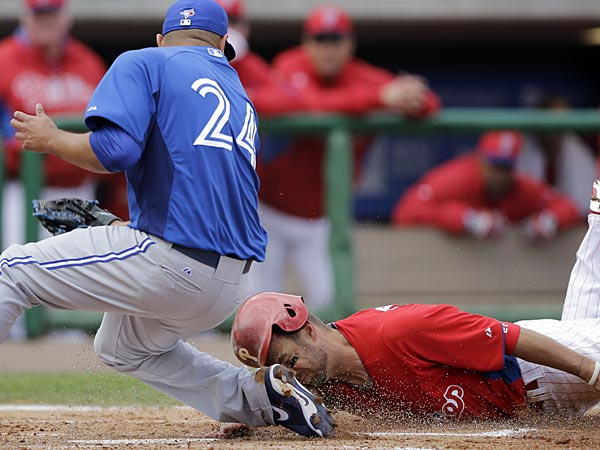 Philadelphia Phillies&acute; Kevin Frandsen, right, slides home to score<br />past Toronto Blue Jays&acute; Ricky Romero on a passed ball during the first<br />inning of a spring training exhibition baseball game on Sunday, March<br />3, 2013, in Clearwater, Fla. (AP Photo/Matt Slocum)