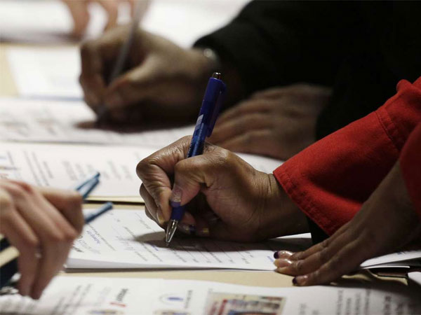 A too-familiar scene still: Applicants filling out forms at a jobs fair in Newark, N.J. (Mark Lenninhan / Associated Press)