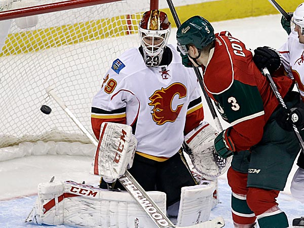The Wild´s Charlie Coyle watches as Jared Spurgeon scores a power play goal on Flames goalie Reto Berra. (Jim Mone/AP)
