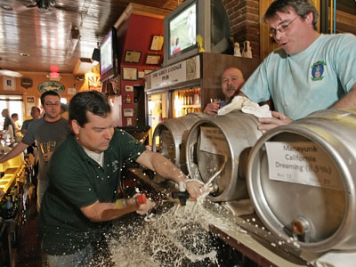 "Mike ""Scoats"" Scotese tapping a firkin, or small keg, of Iron Hill Bourbon Porter on Friday the 13th last year. Suds soaked keggers like it and ""Philly Beer Week"" have made the city the nation´s new beer capitol, according to Maxim magazine. (Michael Bryant / Staff Photographer)"