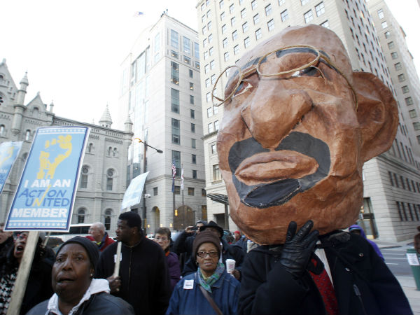 A demonstrator with the a large mask of Philadelphia Mayor Michael Nutter and school supporters protest the possible closer of 29 Philadelphia public schools at City Hall on Tuesday, March 5, 2013. (Yong Kim / Staff Photographer)
