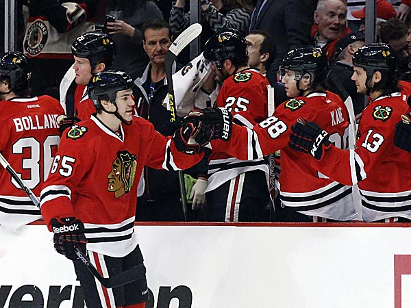 Blackhawks center Andrew Shaw celebrates his goal with teammates on the bench during the first period. (Charles Rex Arbogast/AP)