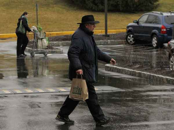 As light rain falls, Greg Shatney of Media heads back to his car at Glen Eagle Square shopping center in Glen Mills late Thursday afternoon.  March 6, 2013. ( MICHAEL S. WIRTZ / Staff Photographer ).