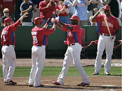 The Phillies´ Ryan Howard (third from left) is congratulated by teammates Eric Bruntlett (left) and Greg Dobbs (second from left) after he hit a three-run homer in the fifth inning against the Tigers. (Eric Mencher/Staff Photographer)