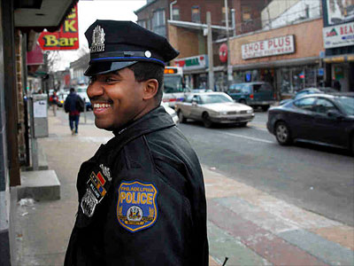 Police Officer Tyshaan Williams walks along Germantown Avenue. Four years ago, when he saw a mother and her infant struggling through the trash on the street, he had to do something. (Laurence Kesterson / Staff Photographer)