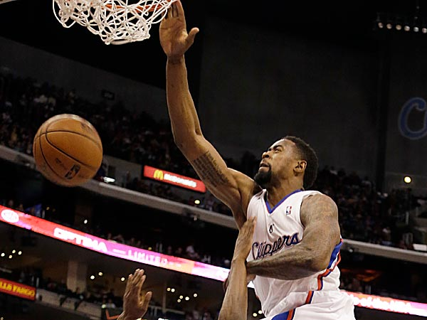 Los Angeles Clippers center DeAndre Jordan dunks the basket and falls on Detroit Pistons guard Brandon Knight. (Reed Saxon/AP)