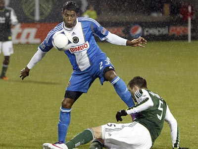 Union forward Lionard Pajoy and Timbers defender Eric Bruner battle for a ball in the first half. (Don Ryan/AP)