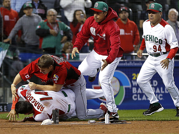 Canada&acute;s Jay Johnson, top left, and Mexico&acute;s Eduardo Arredondo fight<br />during the ninth inning of a World Baseball Classic game, Saturday,<br />March 9, 2013, in Phoenix. (AP Photo/Matt York)