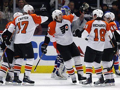 Simon Gagne, center, celebrates with teammates after scoring against the New York Rangers earlier this season. (AP File Photo/Julie Jacobson)