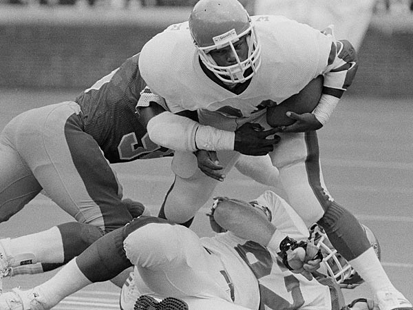 New Jersey Generals Herschel Walker steps over teammate Dave Lapham as he´s held by Stars´ George Cooper in the first quarter of their USFL playoff game in Philadelphia, June 30, 1984. (AP Photo/Rusty Kennedy)