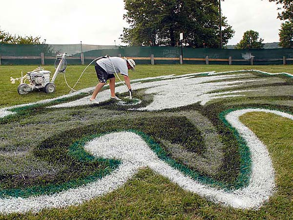Mike Watson repaints the Eagle near the practice fields after a training camp practice at Lehigh University on Mon., July 30. (Yong Kim / Staff Photographer)