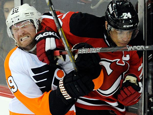 Philadelphia Flyers´ Scott Hartnell, left, runs into the elbow of New Jersey Devils´ Bryce Salvadore during the second period of an NHL hockey game on Wednesday, March 13, 2013, in Newark, N.J. (AP Photo/Bill Kostroun)