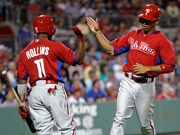Cesar Hernandez is greeted by Jimmy Rollins (11) after scoring on a ground rule double by Ben Revere in the fifth inning of an exhibition baseball game in Fort Myers, Fla., Saturday, March 15, 2014. (Gerald Herbert/AP)