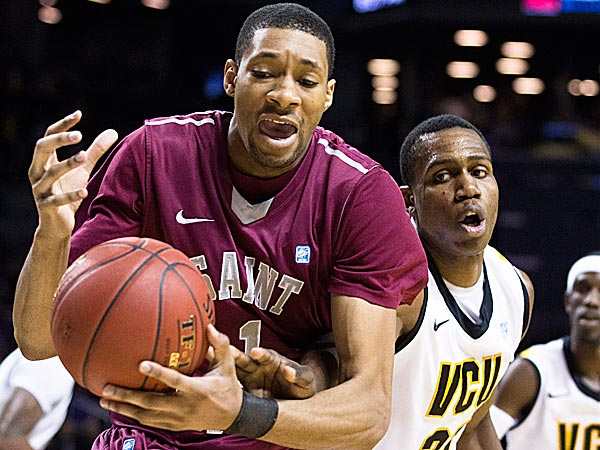 Saint Joseph´s C.J. Aiken protects the ball from the reach of VCU´s Treveon Graham during the second half. (John Minchillo/AP)