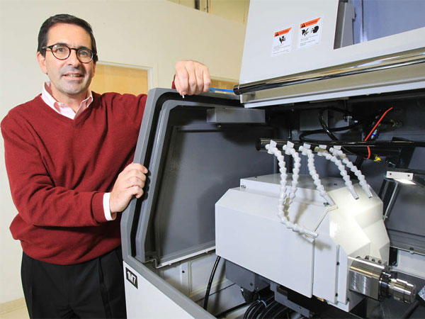 Christopher J. Kneizys , president and CEO of Micro-Coax Inc., in Pottstown, shows a Swiss CNC screw machine, which cuts parts for the connectors that the company makes. (Charles Fox / Staff Photographer)