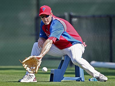 Chase Utley fields grounders while sitting on a bench. (David M. Warren/Staff Photographer)
