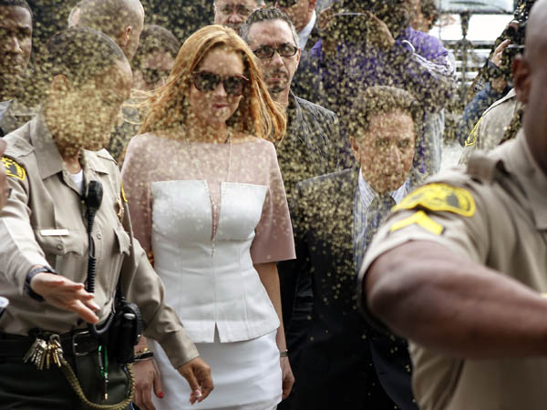 Actress Lindsay Lohan is showered with gold glitter, second left, as she arrives with her attorney Mark Heller, after attending a trial Monday, March 18, 2013, at Los Angeles Superior court. (AP Photo/Damian Dovarganes)