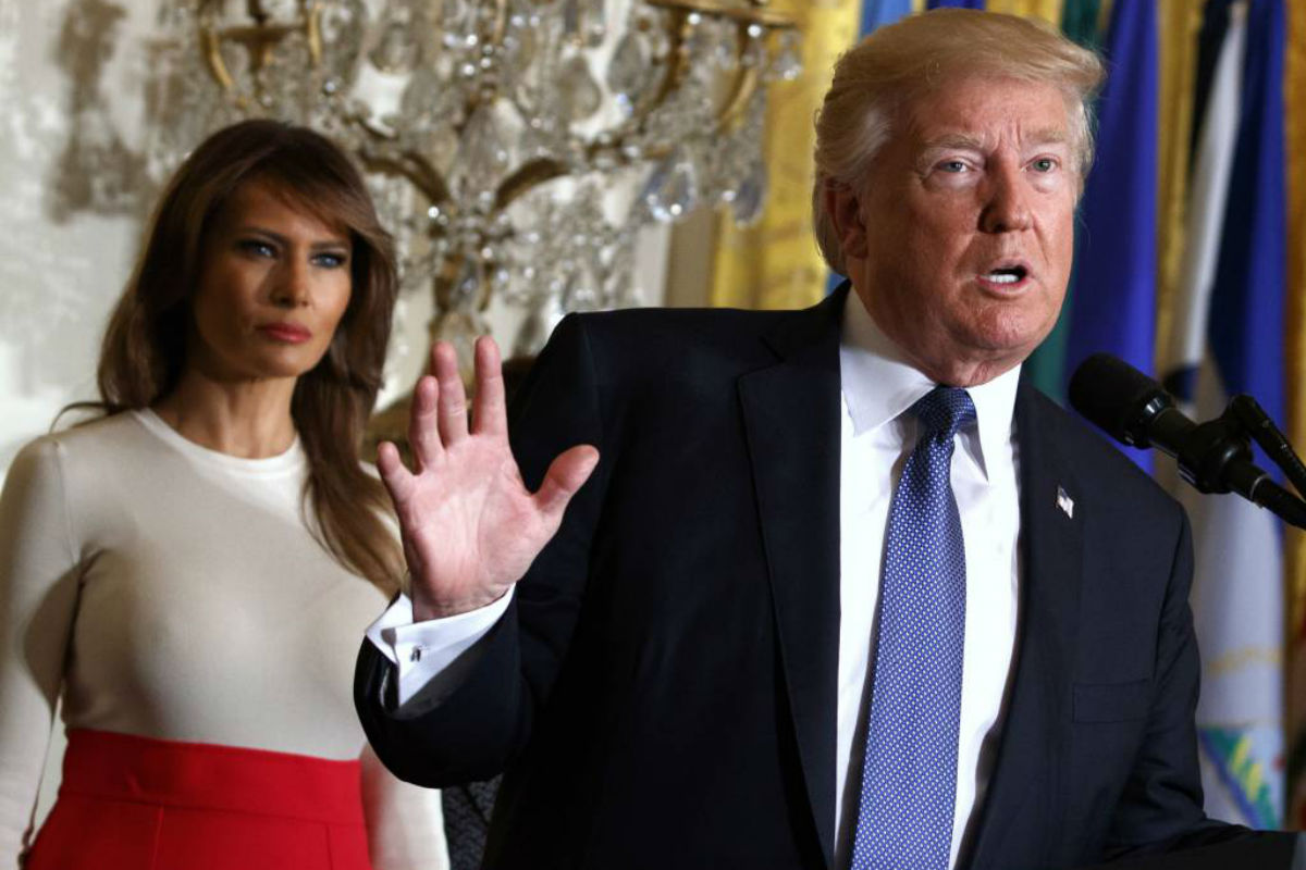 FILE - In this Friday, Oct. 6, 2017, file photo, President Donald Trump speaks during an event at the White House in Washington, as first lady Melania Trump listens. Trump´s plan to combat opioid drug addiction calls for stiffer penalties for drug traffickers, including the death penalty where it´s appropriate under current law. The president is scheduled to unveil his plan Monday, March 19, 2018, in New Hampshire, a state hard-hit by the crisis. He´ll be accompanied by first lady Melania Trump, who has shown an interest in the issue, particularly as it pertains to children.