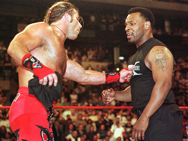 Mike Tyson, right, gets a finger in the chest from wrestler Shawn Michaels during Wrestlemania XIV in Boston Sunday, March 29, 1998. (Winslow Townson/AP file)