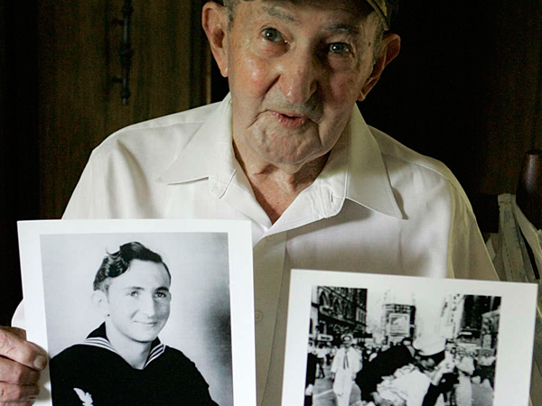 Glenn McDuffie with a portrait of himself and a copy of the iconic shot of a sailor embracing a nurse in Times Square at the end of World War II.