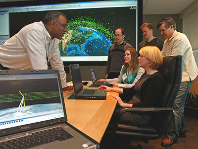 Marc Simmons (left), Ed Mackey, Christie Wichner, Frank Stoner, Amanda Brewer, and Jim Woodburn discuss software that tracks satellites and debris in space from the boardroom at Analytical Graphics Inc. in Exton.
