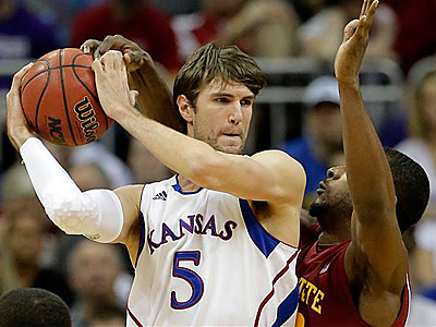 Kansas center Jeff Withey (5) looks to pass the ball around Iowa State forward Anthony Booker during the first half an NCAA college basketball game in the Big 12 men´s tournament on Friday, March 15, 2013, in Kansas City, Mo. (AP Photo/Charlie Riedel)