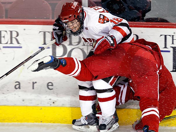 St. Lawrence left winger Kyle Flanagan skates against Nebraska Omaha defenseman Edie DelGrosso during an NCAA college hockey game in Denver at the Wells Fargo Cup, Saturday, Jan. 2, 2010. Nebraska Omaha beat St. Lawrence 3-2 in an overtime shootout victory. (AP Photo/Jack Dempsey)