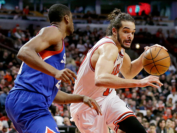 Bulls center Joakim Noah, right, drives to the basket against Philadelphia 76ers forward Thaddeus Young during the second half of an NBA basketball game in Chicago on Saturday, March 22, 2014. The Bulls won 91-81. (Nam Y. Huh/AP)