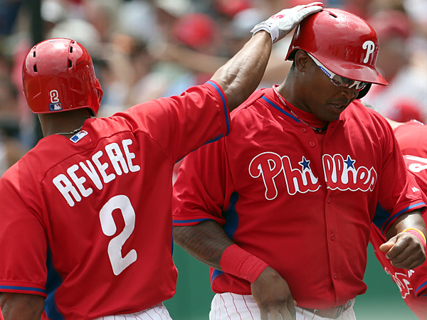 Marlon Byrd gets a tap on the head from Ben Revere after scoring on a sacrifice fly against the Twins. (Yong Kim/Staff Photographer)