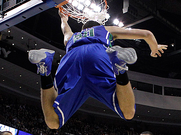 Florida Gulf Coast´s Chase Fieler hangs from the rim after a dunk. (Matt Rourke/AP)