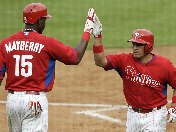 Phillies catcher Carlos Ruiz, right, celebrates with teammate John Mayberry Jr., left, during a spring training game. (Charlie Neibergall/AP)