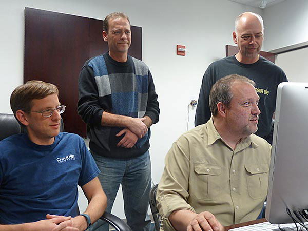 From the left are Aaron Mulder (seated), CEO Mike Rappaport (standing), Ken Rimple (at the computer) and Rod Biresch (standing) at Chariot Solutions. (Bob McGovern / Staff)