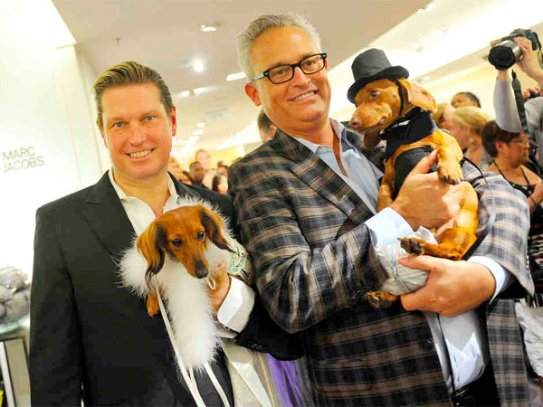 Designers Mark Badgley (left) and James Mischka hold their pooches Rommel and Whiskey at a dog fashion show at Bergdorf Goodman during Fashion Night Out.