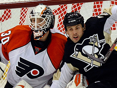 Penguins Craig Adams falls into Johan Backlund during the second period. The Flyers lost to Pittsburgh 4-1.(AP Photo/Keith Srakocic)