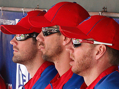 Philadelphia Phillies pitchers Cole Hamels, left, Cliff Lee, center, and Roy Halladay sit in the dugout. (AP Photo/Gene J. Puskar)