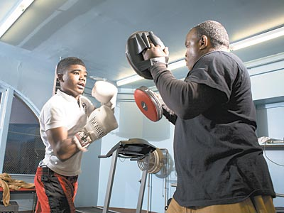 """(Men) need to come out from behind the curtains and skirts and get out there,"" says Men of Tustin president James Haley. Here, Anwar Jones, 15, learns how to box with  William Edney. (ED HILLE / Staff)"