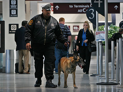 In a reassuring routine, K9 Officer Terry Wright patrols an airport concourse with Rex. (Alejandro A. Alvarez / Staff Photographer)