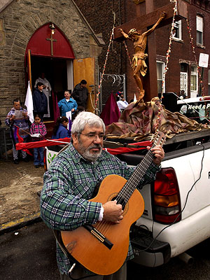 Joaquin Rivera sings and plays a guitar in 2003 before the Good Friday procession. (Gerald S. Williams / Staff Photographer)
