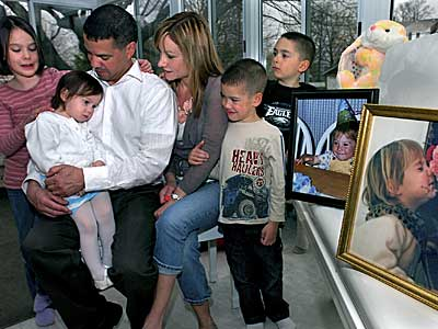 Rob and Patti Pena with Children (from left) Olivia, 9; Eva, 2; Tony, 5, and Robert, 7, alongside photos of Morgan Lee, who died in an auto accident. (Mark C. Psoras/Staff Photographer)