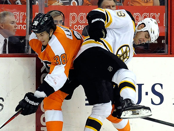 Boston Bruins´ Nathan Horton (18) checks Oliver Lauridsen (38), of Denmark, in the first period of an NHL hockey game, Saturday, March 30, 2013, in Philadelphia. (Michael Perez/AP)