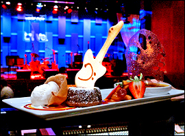 The desserts from Michael Vandergeest, including a brownie sundae, lemon cheesecake, and warm apple cobbler, are whimsically garnished with chocolates and guitar-shaped cookies.                                      (John Costello/Inquirer)