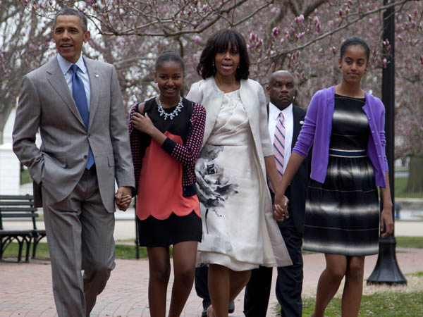 President Barack Obama and first lady Michelle Obama walk from the White House with their daughters Sasha Obama, second from left, and Malia Obama, right, on their way through Lafayette Park to St. John´s Episcopal Church for Easter services, Sunday, March 31, 2013, in Washington. (AP Photo/Carolyn Kaster)