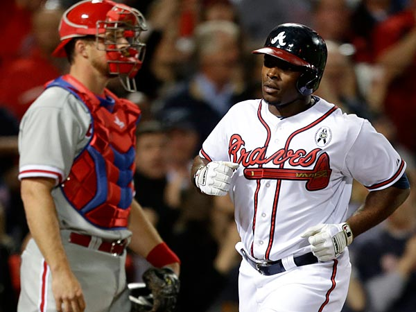 Atlanta Braves´ Justin Upton, right, crosses home plate in front of Philadelphia Phillies catcher Erik Kratz after hitting a home run in the fifth inning. (AP Photo/David Goldman)