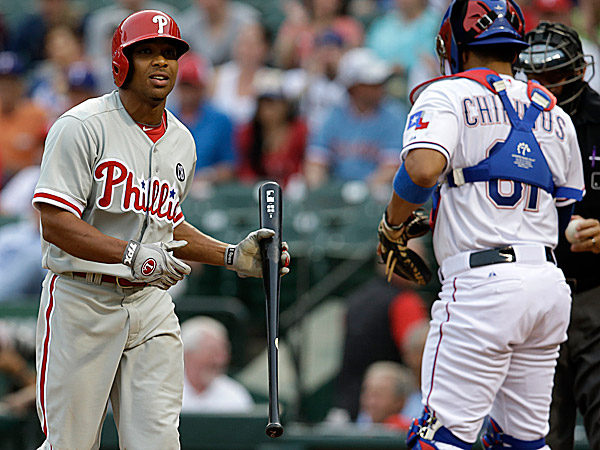The Phillies´ Ben Revere walks back to the dugout past the Rangers´ Robinson Chirinos and home plate umpire Doug Eddings after striking out in the first inning. (Tony Gutierrez/AP)