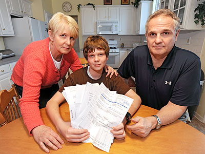 Nancy and Larry Lubas, with son Michael, 15, in the middle, with the stack of bills and correspondence regarding Michael´s brief, 20-minute visit to an emergency room for a jammed finger, which resulted in $2,200 in medical expenses. (Clem Murray / Staff Photographer)